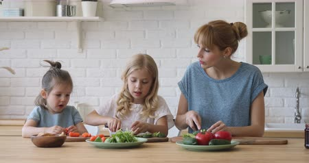 milující : Happy young mommy teaching funny cute little daughters preparing food, chopping fresh vegetables for salad at home. Smiling babysitter chatting with small children girls, cooking together at kitchen.