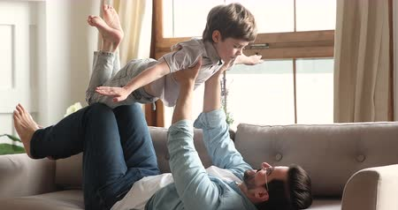 deitado : Cute preschool child boy playing plane game flying in fathers arms enjoying good time together with parent at home, happy dad lifting little kid son up bonding together lounge on sofa in living room