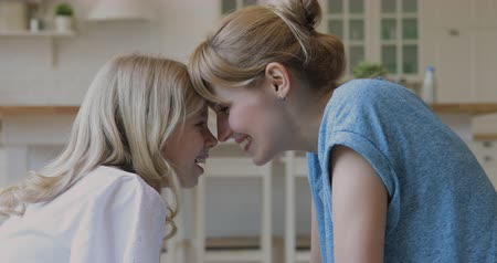 milující : Side view playful young single mommy touching noses with happy blonde little daughter. Smiling loving family of two enjoying sweet tender moment together on couch, spending weekend time at home. Dostupné videozáznamy