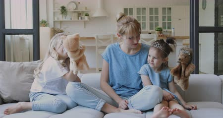 Деятельность выходные : Happy young mommy sitting on couch with cute little blonde daughters, playing with puppet toys. Laughing nanny babysitter having fun with small kids girls wearing crowns, bonding together at home.