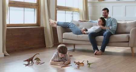 ısıtma : Cute little preschool kid son drawing on warm floor while young parents couple relaxing on sofa in modern living room, barefoot family enjoy leisure activities underfloor heating in apartment at home