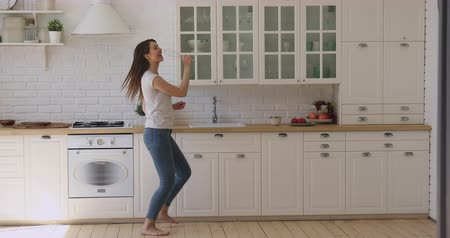 cantar : Full length overjoyed smiling woman having fun in kitchen, dancing to favorite music. Excited carefree funny millennial girl singing pop song in whisk while preparing breakfast, cooking meal alone.