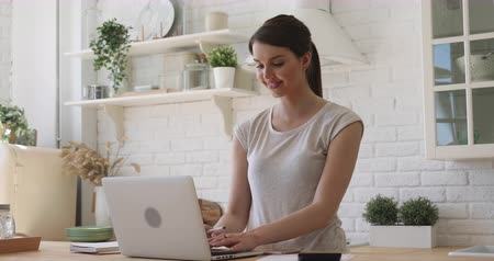 monitoração : Attractive focused girl reading pleasant email, working remotely on computer in modern kitchen. Smiling young woman looking at laptop screen, answering messages, chatting with clients or friends. Stock Footage