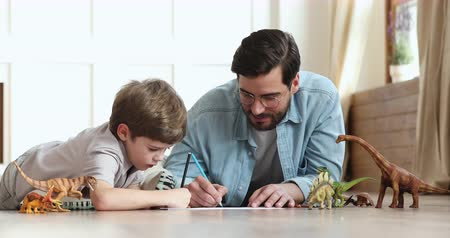 ısıtma : Caring young adult father playing with preschooler child son help teach drawing pencils enjoy single parent and little kid creative lifestyle activity together lying on warm floor at home apartment Stok Video