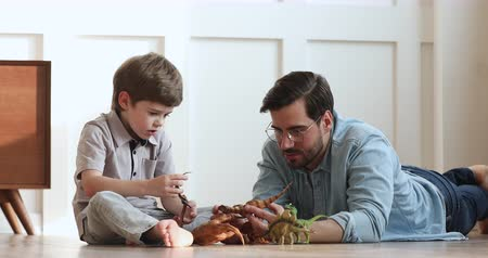 ısıtma : Loving young adult dad and cute preschool child son talking playing dinosaurs toys sit on warm floor, happy single parent father helping little kid explain paleontology having fun at home together Stok Video