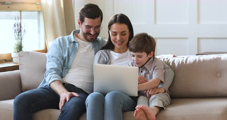 três pessoas : Happy family young parents couple and cute preschool kid son using laptop looking at computer screen enjoying watching funny social media video doing online shopping relaxing on sofa at home together Vídeos
