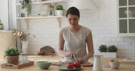 okurka : Smiling pleasant young woman enjoying cooking alone at home. Happy fit millennial housewife chopping fresh vegetables, preparing salad or healthy vegetarian vegan diet food in modern kitchen.