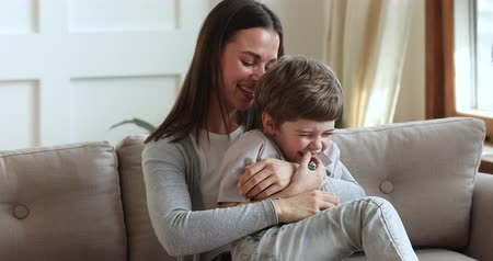 hugs : Happy family adult mother tickling cute small child son laughing playing together on sofa in living room, young mum and little preschool kid boy having fun cuddle enjoy lifestyle game relax on couch