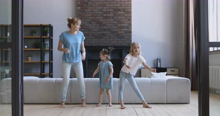 nanny : Full length happy young woman dancing barefoot on warm wooden floor with overjoyed daughters in living room. Excited little girls imitating moves of mommy nanny, enjoying activity together at home. Stock Footage