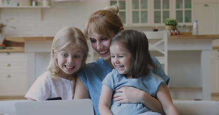 karikatury : Addicted to technology smiling young mother embracing two little daughters, looking at laptop screen. Happy millennial nanny babysitter enjoying watching cartoons with children together at home.