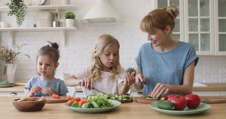 puericultura : Happy little girl eating vegetables while eldest sister preparing salad with caring mommy at kitchen. Cheerful pleasant young babysitter nanny talking to small sisters, teaching cooking food.