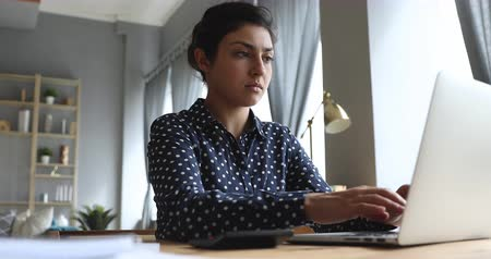 calcular : Serious young indian woman calculate domestic bills pay loan payment online on laptop sit at home office desk, focused businesswoman using computer calculator plan expenses manage finances concept