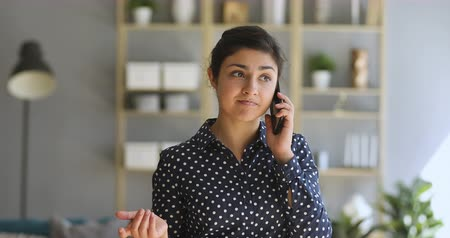 hívó : Young indian woman make call standing at home office, ethnic female entrepreneur holding cellphone having mobile conversation talking on the phone speaking communicating by smartphone indoors