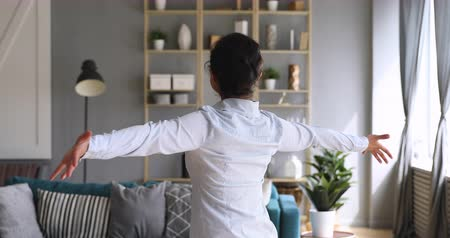 やる気 : Happy overjoyed first time home owner young indian woman spin dance alone with arms outstretched in modern living room interior enjoy freedom having fun in new flat, investment, independence concept