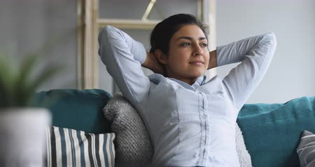 respiração : Relaxed serene healthy young indian woman resting on comfortable sofa hands behind head breathing fresh air looking dreaming lounge on couch in living room enjoy stress free day peace of mind at home Vídeos