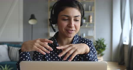 fejhallgató : Happy indian young woman wear headset communicating by conference call speak looking at computer at home office, video chat job interview or distance language course class with online teacher concept