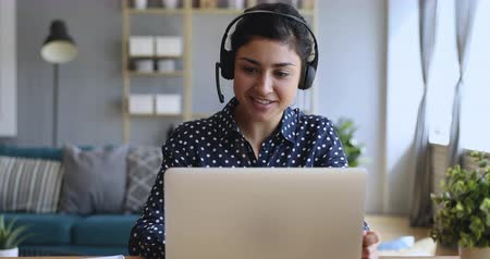 előléptetés : Smiling indian young business woman wear wireless headset video conference calling on laptop computer talk by webcam in online chat, customer support service and distance online teaching concept Stock mozgókép