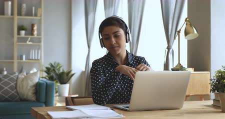 учение : Focused indian woman distance teacher online tutor wear headphone conferencing on laptop communicate with student by webcam video call chat explain course help e learning computer education concept