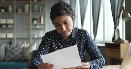 敗者 : Upset stressed indian ethnic girl feel frustrated open envelope at home reading bad news receive paper post mail letter about financial problem, bank debt bill, failed exam test results or subpoena