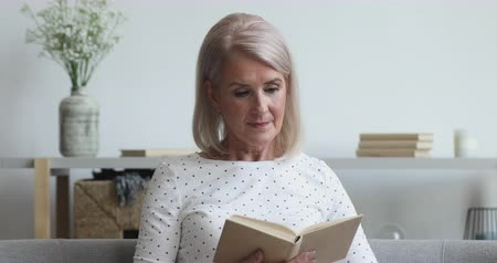 literatuur : Serious happy middle aged old woman relaxing holding reading book sit on sofa at home, smiling senior adult lady enjoying spending leisure time with modern novel literature on couch in living room