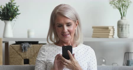 lezing : Happy middle aged mature woman holding smart phone looking at cellphone screen playing mobile games using social media apps in smartphone sit on couch at home, older people and technology concept Stockvideo