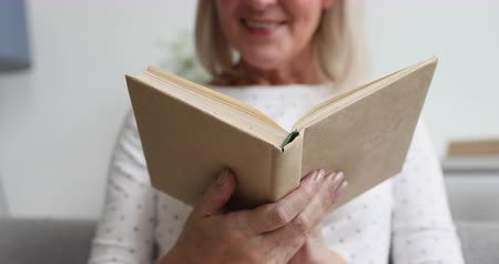stories : Happy old senior woman relaxing holding in hands reading open book concept turning pages at home, smiling middle aged adult lady enjoying modern novel literature, close up view, focus on book Stock Footage