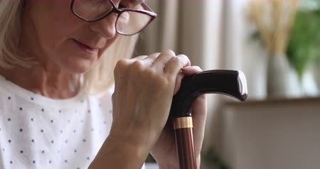nyomott : Upset old senior woman hold cane stick feel sad depressed about health problem sit alone at home near window wait caregiver visit, frustrated grandmother worried of disease concept, close up view