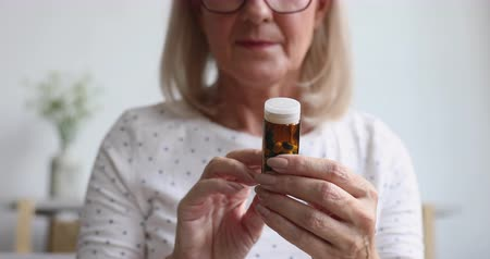 lezing : Sick ill old senior woman hold painkiller pill bottle read prescription side effect take medicine meds to relieve pain in mature grandma hands, older people pharmacy medicament concept, close up view