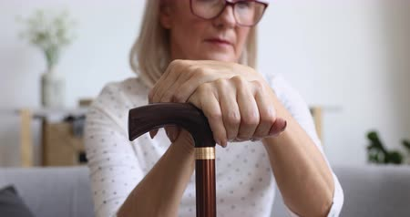 osamělost : Retired old disabled mature woman holding cane stick in hands sit alone on sofa at home, senior elderly aged lonely grandmother having older age osteoporosis health problems concept, close up view