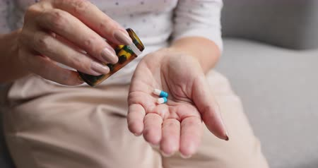 таблетки : Old senior woman pouring two pills from meds bottle hold painkiller capsules on hand take medicine to relieve pain, mature elderly grandmother healthcare, pharmacy medication concept, close up view