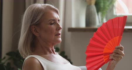 aparelho : Overheated old senior woman feel hot wave fan annoyed with high temperature sit at home, stressed middle aged lady sweating suffer from climax summer weather heat problem without no air conditioner