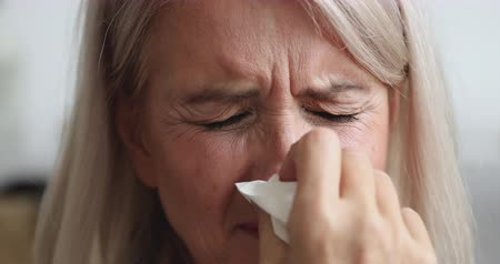 zsebkendő : Allergic ill old mature woman hold tissue sneezing got fever caught cold blowing running nose in handkerchief, sick middle aged lady having flu symptom cough at home, allergy concept, close up view Stock mozgókép