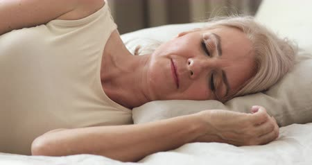 отель : Calm serene healthy mature middle aged woman resting alone sleeping well in comfortable bed lying asleep on soft pillow relax on orthopedic mattress enjoy good night sleep concept, close up view