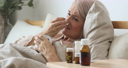 zsebkendő : Ill upset mature old woman sneeze blow running nose hold tissue got flu concept caught cold sit on bed, sick senior lady have health problem flue symptoms coughing take medicine drink hot tea at home