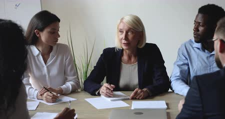 cursos : Older middle aged female leader mentor executive conduct corporate briefing speak sit at diverse group briefing table explain company strategy planning project training staff team in conference room Stock Footage