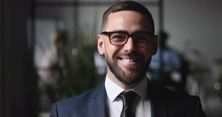 тренер : Confident smiling businessman professional ceo leader wear glasses suit standing looking at camera, happy male executive company owner corporate manager posing in office, close up business portrait