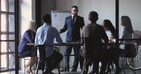 speaker : Smiling businessman professional leader conference speaker wear suit give business presentation teach diverse executive group explain corporate strategy at office meeting workshop training concept Stock Footage