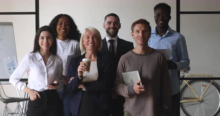 empregador : Happy multiracial business team of old young african caucasian people stand together looking at camera in office, smiling diverse professional colleague staff group corporate portrait, human resource Stock Footage