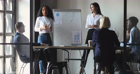 cursos : African and caucasian female speakers speak give flip chart office presentation at boardroom meeting, diverse business coaches presenters work in teamwork at conference workshop seminar training
