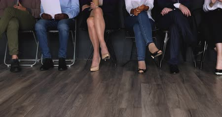 etnia africano : Diverse professional business people group sit on chairs in row line queue waiting for their turn on job interview, multiracial applicants legs close up view, human resources and recruitment concept