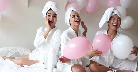 отель : Excited carefree diverse young girls women wear dressing gowns towels on head looking at camera holding balloons feel overjoyed laugh enjoy hen spa pajama slumber sorority party together sit on bed