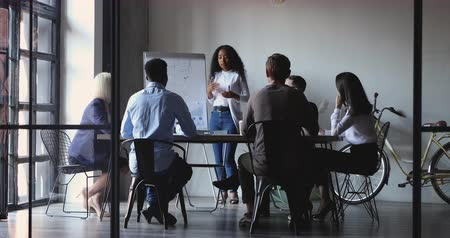 speaker : African female conference speaker presenter give business presentation explain project plan on whiteboard teaching diverse team group at office boardroom meeting training in modern creative office Stock Footage