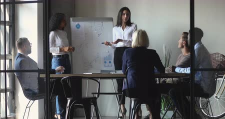 тренер : Caucasian female coach training multiracial people group work in team with african presenter, two diverse speakers team give presentation on flip chart explain strategy at office workshop meeting