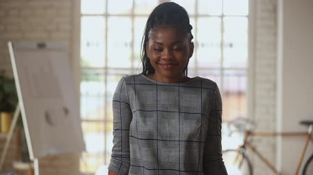 konsultant : Serious young african ethnicity business woman looking at camera, starting smiling, listening to good news. Confident mixed race international company female employee, corporate leader boss portrait.