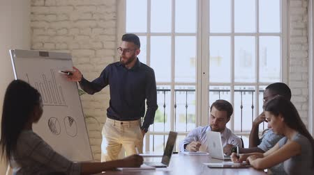 speaker : Focused mixed race employees participating in educational lecture. Confident arabian speaker presenting marketing strategy plan to concentrated investors clients, writing down notes in boardroom. Stock Footage