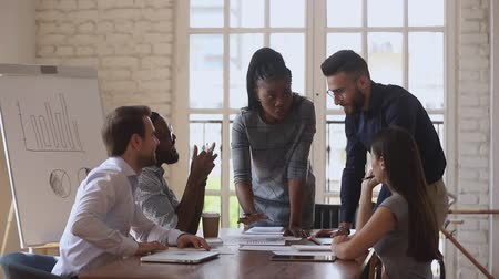 partnerzy : Smiling multiracial employees listening to young female african american team leader joking at brainstorming meeting. Confident biracial business woman instructing newbie intern in boardroom. Wideo