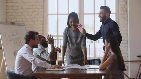 общий : Diverse teammates watching cheerful young arabian manager giving high five to biracial colleague, coming to common decision agreement at mixed race business people brainstorming meeting in office.