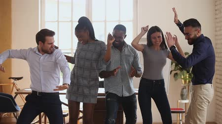 multirracial : Happy diverse business people dancing at office, celebrating corporate achievement. Overjoyed young mixed race international company staff having fun, enjoying Friday party together at workplace.