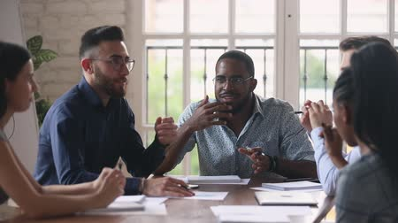 collaborating : Excited group of multiracial professionals discussing project ideas at brainstorming meeting in office. Emotional african american young team leader in eyewear negotiating working issues in boardroom. Stock Footage