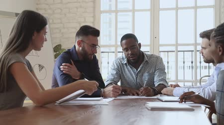 lider : Motivated focused young african ethnicity boss team leader sitting at table with diverse colleagues, negotiating project details, discussing marketing strategy, making notes on paper documents. Stok Video